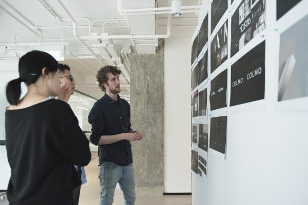 Three People Viewing Wall of COLMO Related Images